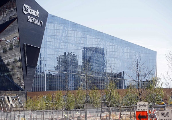 Downtown Minneapolis is reflected and newly planted trees line the park which adjoins the U.S. Bank Stadium, the new stadium for the home to the Minne