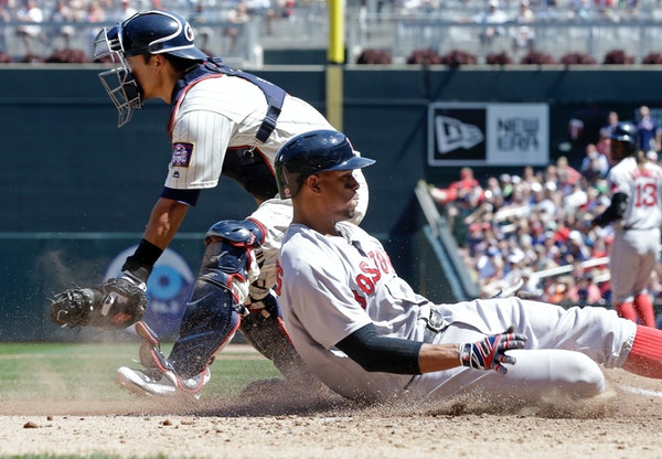 Boston Red Sox's Xander Bogaerts, right, scores from third on a go-ahead run past Minnesota Twins catcher Kurt Suzuki on a sacrifice fly by Hanley Ram