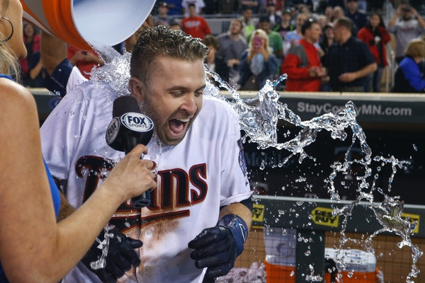 Minnesota Twins' Brian Dozier receives a bucket of water over his head during an interview after he hit a two-run home run to defeat the Miami Marlins