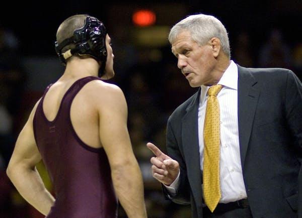 Gophers wrestling coach J Robinson talks with a U wrestler.