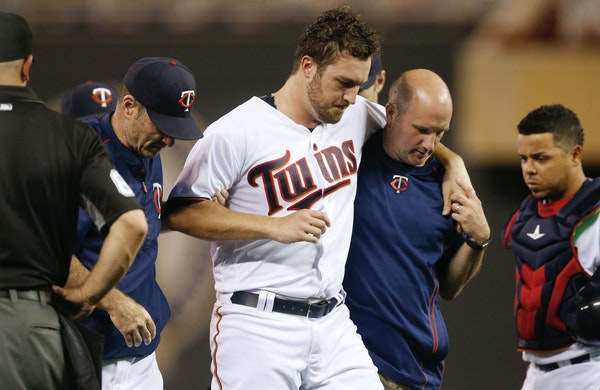 Minnesota Twins pitcher Phil Hughes is helped off the field by trainer Tony Leo, right, and manager Paul Molitor, left, after he was hit in the knee w