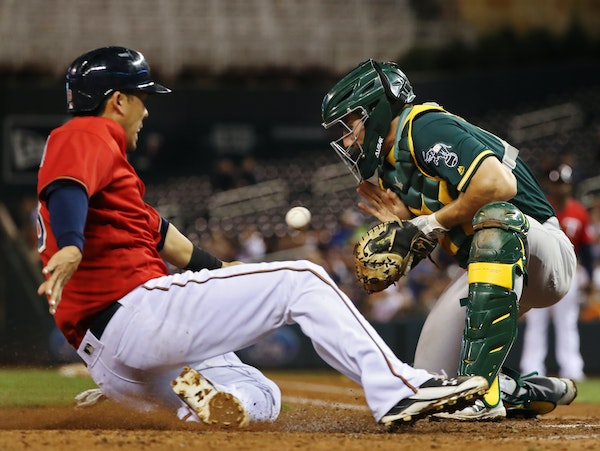 The Twins' Kurt Suzuki scored before Oakland catcher Matt McBride could apply the tag in the fourth inning of Minnesota's 11-4 victory at Target Field