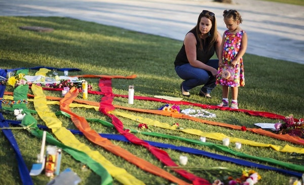 Rhonda Rodeffer, left, and her daughter Kennedy, 4, visit a makeshift memorial for the victims of a mass shooting at the Pulse nightclub Tuesday, June