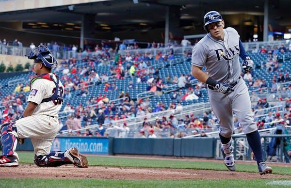 Tampa Bay Rays' Logan Morrison runs around Minnesota Twins catcher Juan Centeno, left, after scoring on his three-run home run off Twins' Michael Tonk