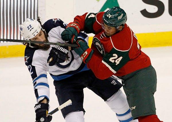 Minnesota Wild defenseman Matt Dumba (24) hits Winnipeg Jets right wing Chris Thorburn (22) during the first period of an NHL hockey game in St. Paul,