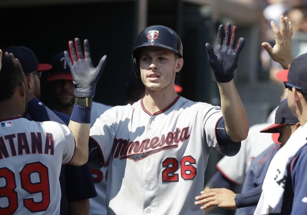 Minnesota Twins' Max Kepler is congratulated in the dugout after his solo home run during the ninth inning of a baseball game against the Detroit Tige