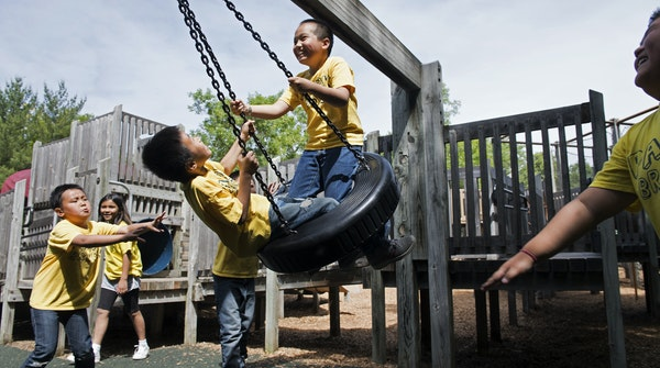 kicker here: Park Brook 3rd graders Drake Thammavongsa, left, and Aaron Vu are pushed on the tire swing by Elvin Yang, far left, and other elementary