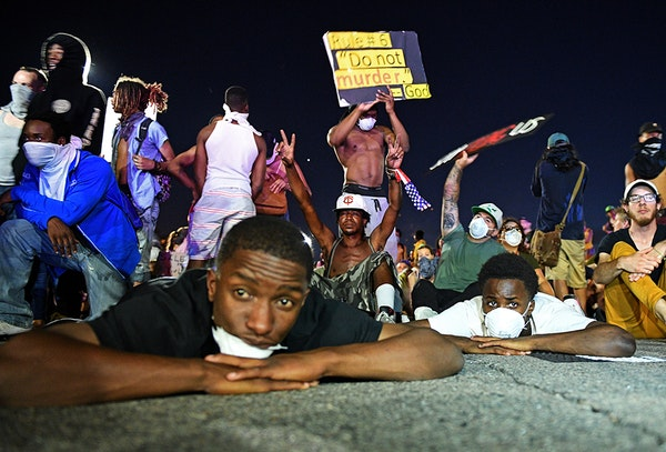 Protesters laid and sat on the ground in front of the police line on I-94 near the Dale St. exit on Saturday night.
