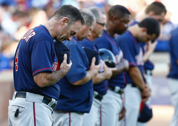 Members of the Minnesota Twins including manager Paul Molitor observe a moment of silence in remembrance of the officers killed and injured in Dallas.