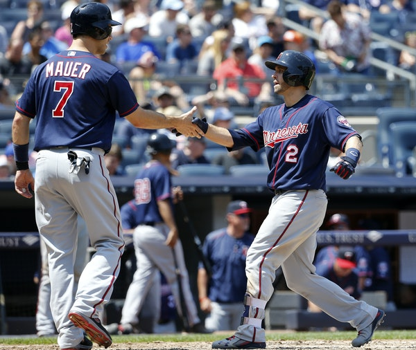 Minnesota Twins designated hitter Joe Mauer (7) greets teammate Brian Dozier (2) after scoring on Dozier's two-run home run during the sixth inning of