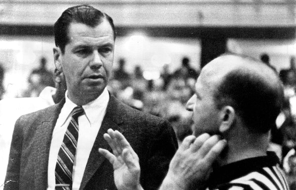 John Kundla, talking with NBA referee Sid Borgia during a game in 1959, was initially reluctant to take the Lakers coaching job, but he was finally pe