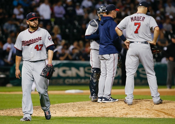 Minnesota Twins starter Ricky Nolasco, left, leaves the baseball game after handing off the ball to manager Paul Molitor during the sixth inning again