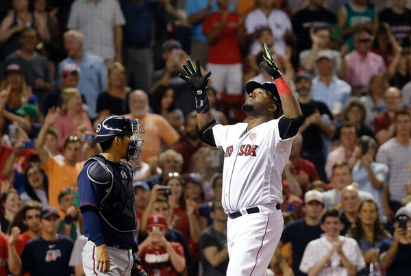 Boston Red Sox designated hitter David Ortiz gestures at the plate in front of Minnesota Twins catcher Kurt Suzuki after hitting a two-run homer in th