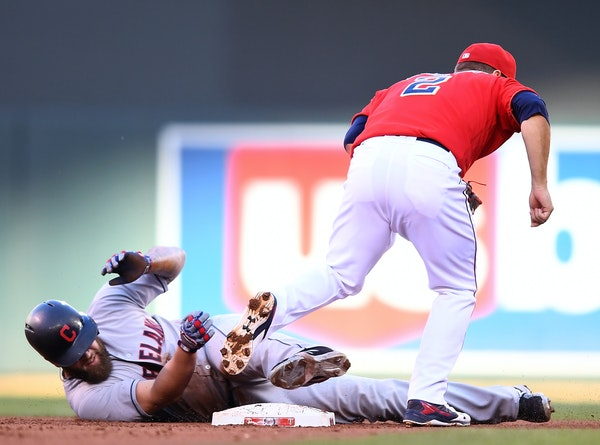 Cleveland Indians first baseman Mike Napoli (26) slid past first after being tagged out by Minnesota Twins second baseman Brian Dozier (2) after nearl