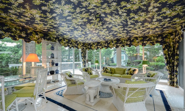 The floral-canopied porch features views of a private pond.
