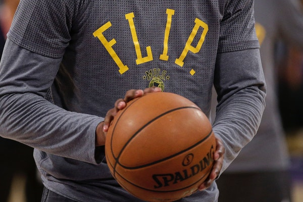 Los Angeles Lakers' Kobe Bryant wears a t-shirt in honor of Flip Saunders during pre-game warmups before an NBA basketball game with the Minnesota Tim