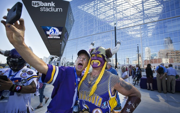 Vikings fans Larry Spooner, of Plymouth, left, and Syd Davy of Vancouver, British Columbia, posed Friday in front of U.S. Bank Stadium on opening day.