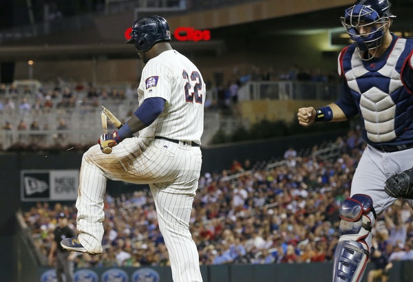 Atlanta Braves catcher A.J. Pierzynski, right, pumps his fist as Minnesota Twins' Miguel Sano, left, breaks his bat over his leg after striking out to