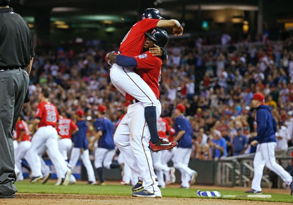Minnesota Twins' Eddie Rosario is hoisted by Miguel Sano after he scored the winning run on a bases-loaded walk by Chicago White Sox pitcher Tommy Kah