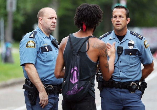 Protester Jabob Ladda, center, negotiates peacefully with St. Paul Police East Patrol commander Steve Anderson, left, and St. Paul Police senior comma