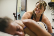 Laura Johnson and Bri Dube joked during a fascia stretch therapy session. Johnson relies on soothing speech to keep clients relaxed and at ease.