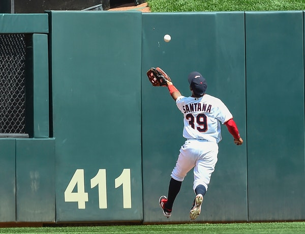 Minnesota Twins center fielder Danny Santana misses a fly ball hit by Cleveland Indians' Abraham Almonte and ruled a double after bouncing over the fe