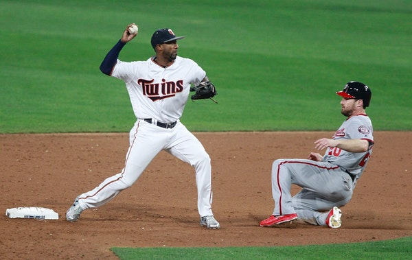 Minnesota Twins second baseman Eduardo Nunez, left, throws to first base to complete a double play after forcing out the Washington Nationals' Daniel
