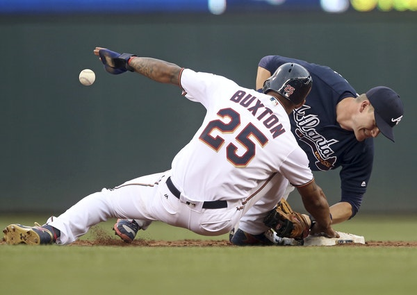 Atlanta Braves second baseman Gordon Beckham right, loses the ball as he attempts to tag Minnesota Twins' Byron Buxton off the base as Buxton returned