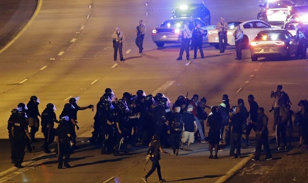 Police confront protesters blocking I-277 during a third night of unrest following Tuesday's police shooting of Keith Lamont Scott in Charlotte, N.C.,