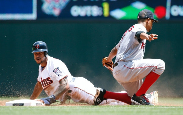 Minnesota Twins' Byron Buxton, left, is safe stealing second base after a late tag by Boston Red Sox shortstop Xander Bogaerts, right, during the seco