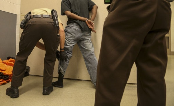 A recently arrested man is searched in the holding area of the Hennepin County jail earlier this summer.