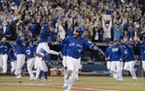 Toronto Blue Jays' Edwin Encarnacion celebrates while he rounds the bases after hitting a walk-off three-run home run during the 11th inning of an Ame