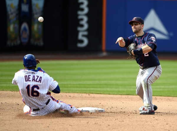 Minnesota Twins second baseman Brian Dozier forces out New York Mets Alejandro De Aza and throws to first base to complete the double play in the fift