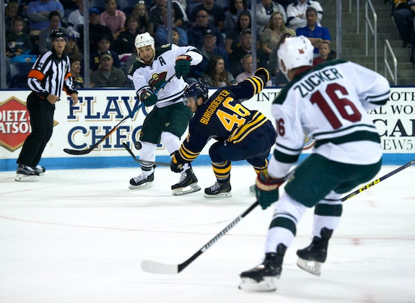 The Wild's Chris Stewart passed to Jason Zucker as the Sabres' Erik Burgdoerfer defended during an NHL exhibition game Monday in State College, Pa. Zu