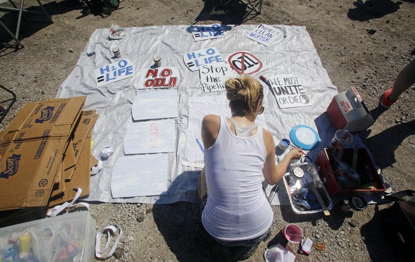 Casey Stinenetz of St. Louis painted signs against the Dakota Access Pipeline for a protest in Montrose, Iowa.