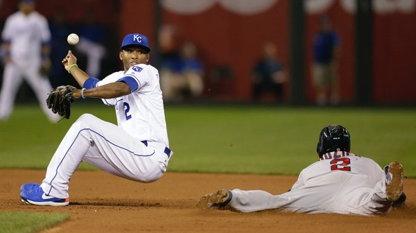Royals shortstop Alcides Escobar was unable to hold a wide throw as the Twins' Brian Dozier stole second base during the ninth inning Tuesday. The Roy