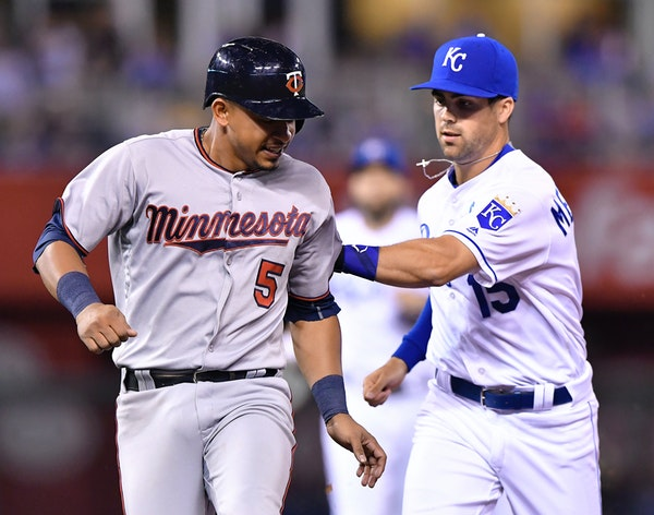 Royals second baseman Whit Merrifield, right, tagged out the Twins' Eduardo Escobar on an attempted steal and rundown in the fifth inning Wednesday ni