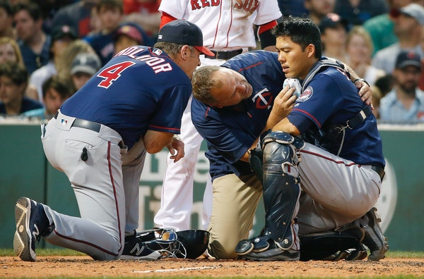 Minnesota Twins manager Paul Molitor (4) and a trainer tend to Kurt Suzuki, right, who was injured on a pitch during the second inning of a baseball g
