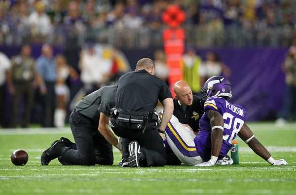 Adrian Peterson is tended to by the training staff after his knee injury in the third quarter of Sunday's game.