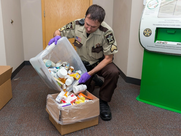 A Hennepin County sheriff's deputy disposed of prescription drugs. To aid this process, 30,000 deactivation pouches are being handed out to those wh