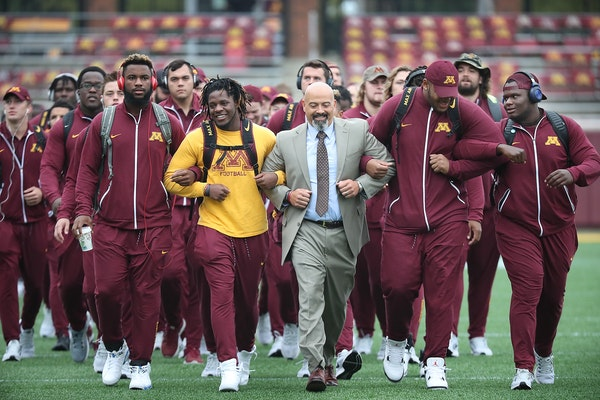 Eric Klein, center, the head strength and conditioning coach, led the team onto the field before the Gophers took on Colorado State at TCF Bank Stadiu