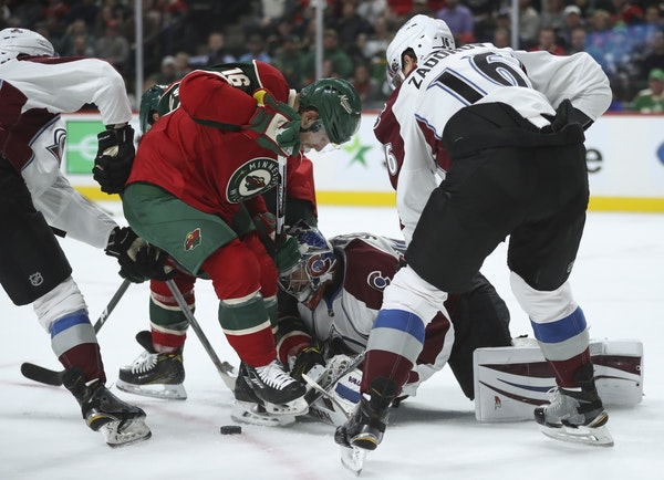 Minnesota Wild left wing Jason Zucker (16) and Colorado Avalanche goalie Jeremy Smith (40) went after a puck well out of the crease in the first perio