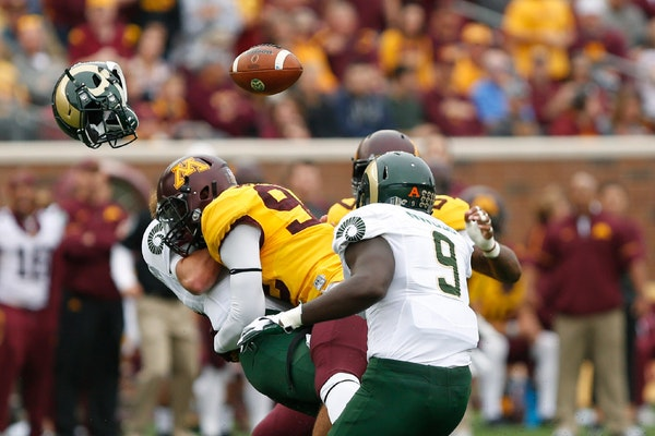 Colorado State quarterback Collin Hill loses his helmet and football after being tackled by Minnesota defensive lineman Tai'yon Devers during an NCAA