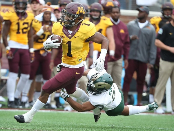 Minnesota's running back Rodney Smith carried the ball for a first down despite defensive pressure by Colorado State's defensive back Justin Sweet in