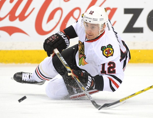 Chicago Blackhawks left wing Tomas Fleischmann (12) passed away the puck as he fell to the ice in the first period.
