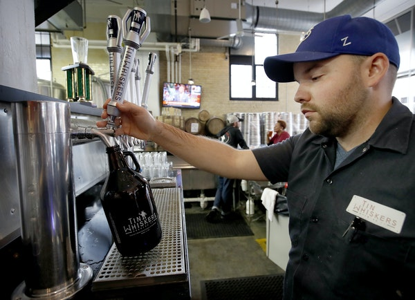 Bartender Ben Kampa filled a growler at Tin Whiskers in St. Paul, one brewery that would benefit from longer sale hours.
