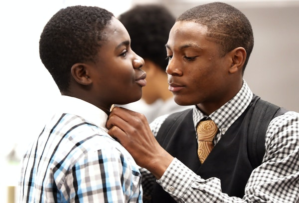 Emmanuel Ogboru right a senior receiver at Cooper High School Wednesday helped freshman Manasseh Williams with his shirt during dressed for success We