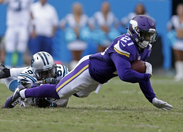 Minnesota Vikings' Jerick McKinnon (21) is tackled by Carolina Panthers' Mario Addison (97) in the second half of an NFL football game in Charlotte, N