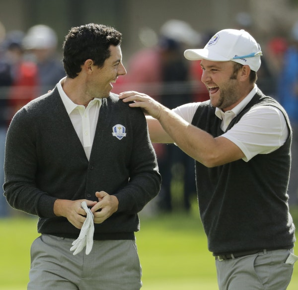Andy Sullivan, right, perhaps sought some magic to rub off after Euro teammate Rory McIlroy holed his approach shot for an eagle Thursday.