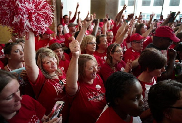 About 100 Allina Health nurses including Denise Frovarp (with pom poms) from Mercy Hospital in Coon Rapids, marched through the Capella building to de